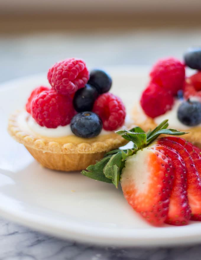 a mini tart piled with raspberries and blueberries on a plate with a sliced strawberry