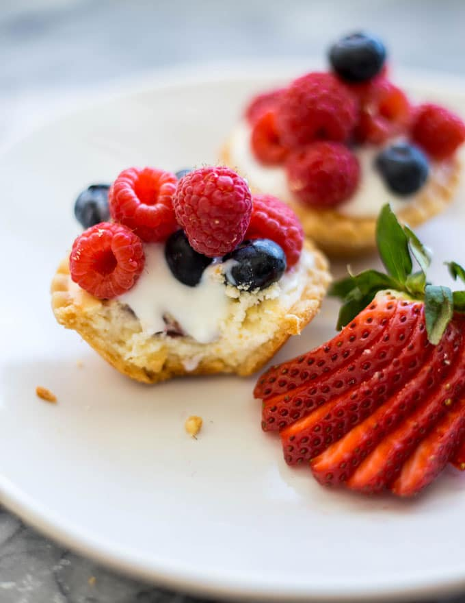 a mini tart with a bite taken out topped with yogurt, raspberries, and blueberries on a plate with a strawbery