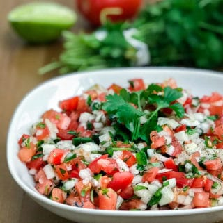 a bowl of pico de gallo with limes, cilantro, and a tomato in the background